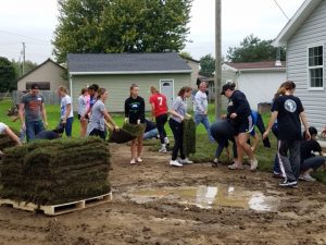 Volunteers laying sod at the Habitat for Humanity build